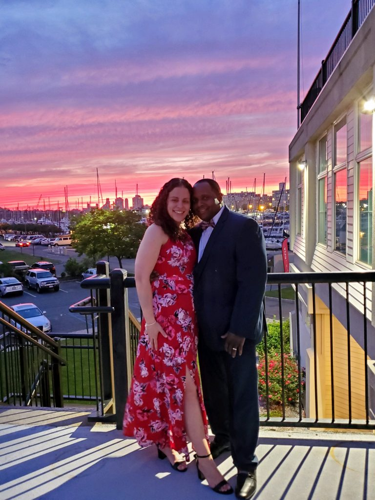 Couple at wedding at Maritime Parc, posing in front of the sunset.