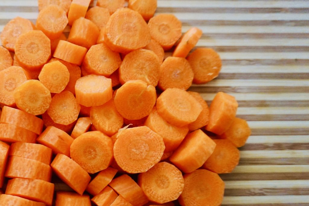 Carrots cut into small pieces on a cutting board.