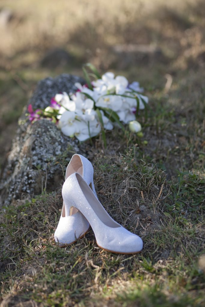 White bridal shoes and bouquet in the grass outside.