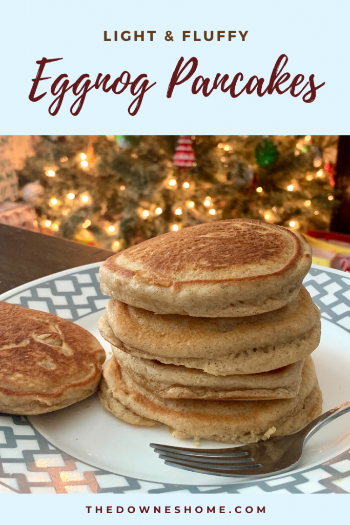 Fluffy eggnog pancakes stack in front of Christmas tree.