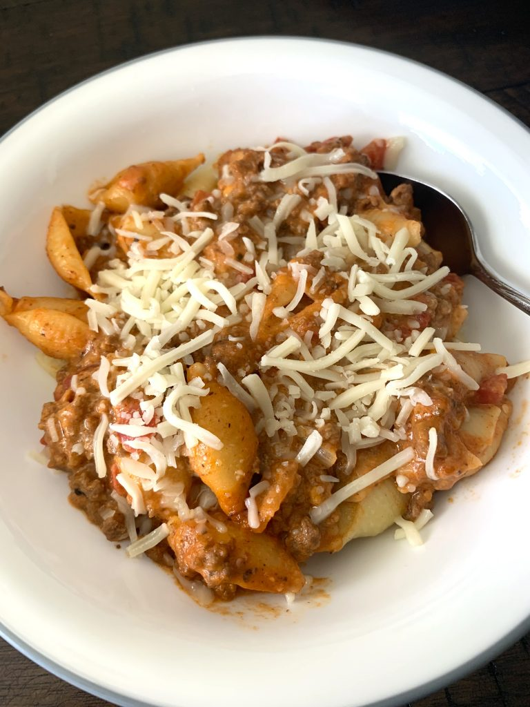 Cheesy beef pasta in bowl with spoon.