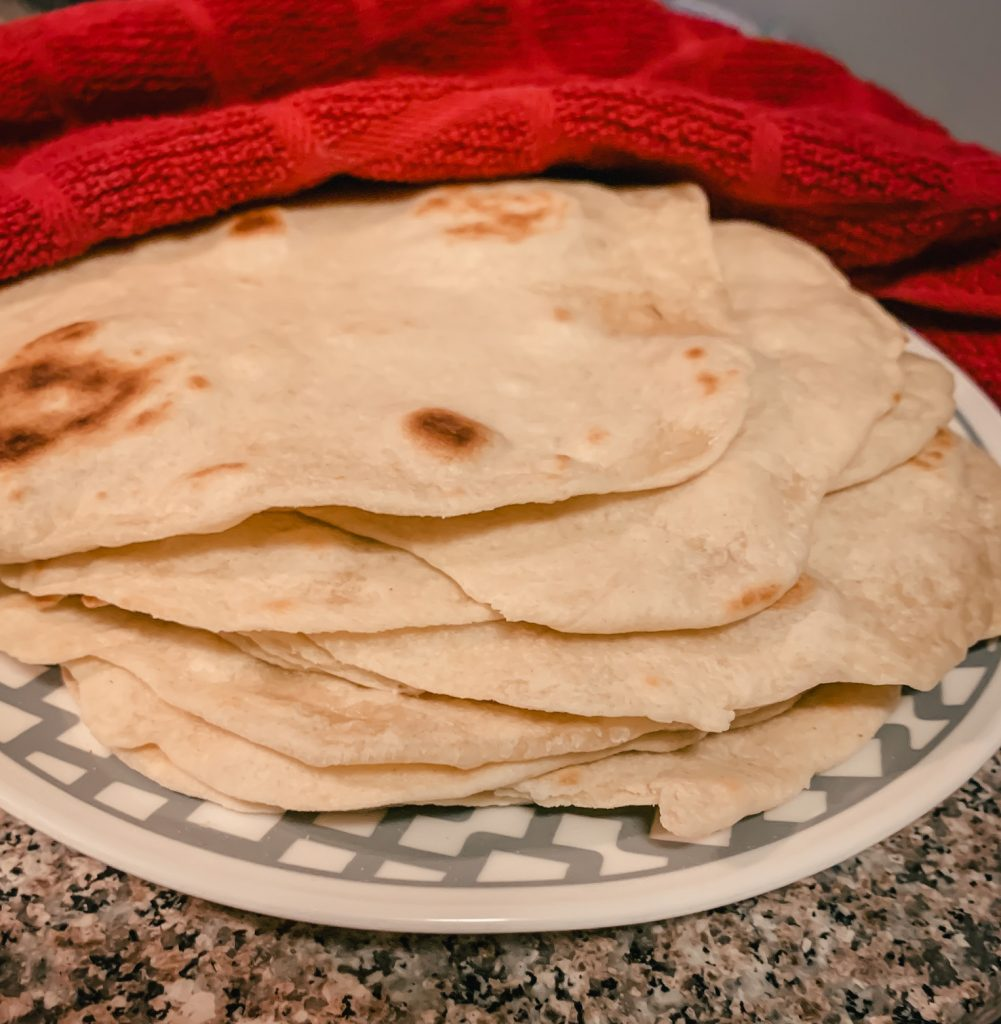 Flour tortillas on plate with dish towel.