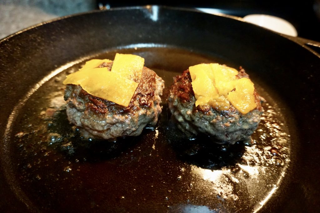 Burgers cooking in pan with cheese.