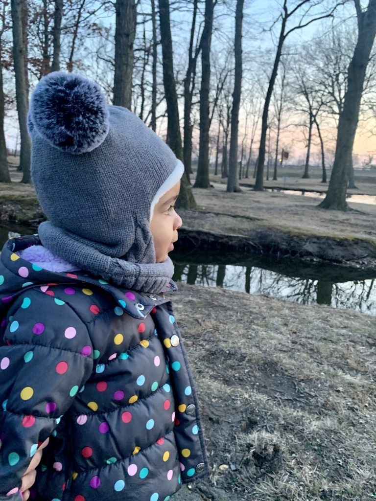 Little girl in the park, looking at the sunset on International Women's Day