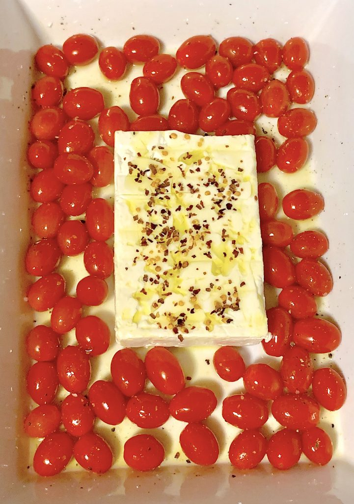 Feta and tomatoes in baking pan